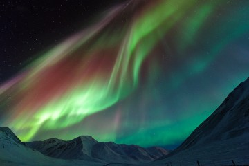 Adventure Travel Photo of the Day - www.letsbewild.com - Symphony of Lights: Northern Lights over Alaska's Atigun Pass - Tom Charoensinphon